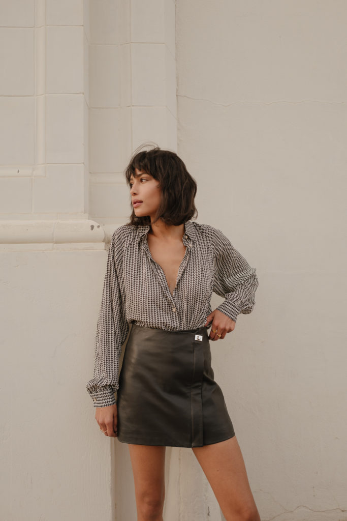 Lauren Johnson of Disco Daydream wears a houndstooth top and leather skirt for fall from REISS